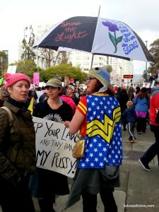 "Wonder Woman protesting with umbrella that is painted with a flower and ""They tried to bury us they didn't know we are seeds"""