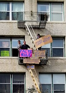 "Dudes on fire escape with signs: FACTS RULE, and ""Make Signs Great Again"""
