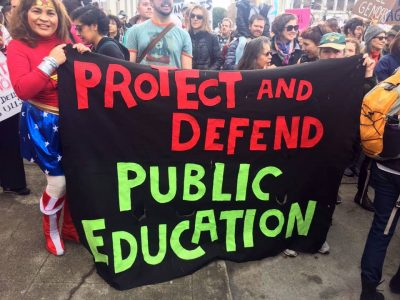 woman dressed as Wonder Woman holding huge banner: Protect and Devent Public Education