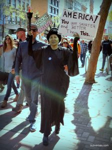"""woman dressed as the statue of liberty with sign"""" """"America! You are smarter and better than this!"""""""