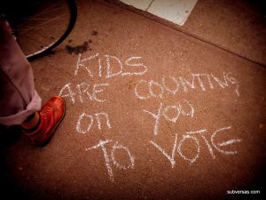 "Sidewalk chalk that reads ""kids are counting on you to vote."""
