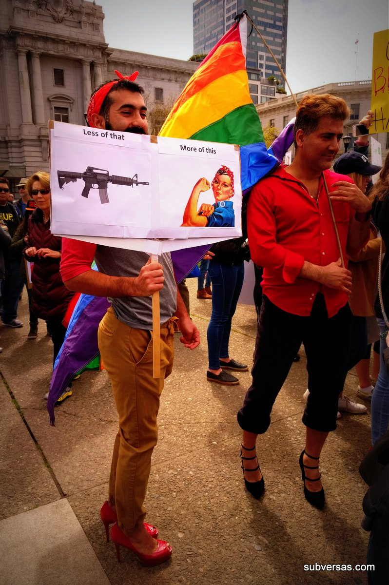 """Dude in heels with sign: """"Less of this [pic of gun] More of This [pic of Rosie the Riveter]"""" standing next to guy in heels waving the rainbow flag."""