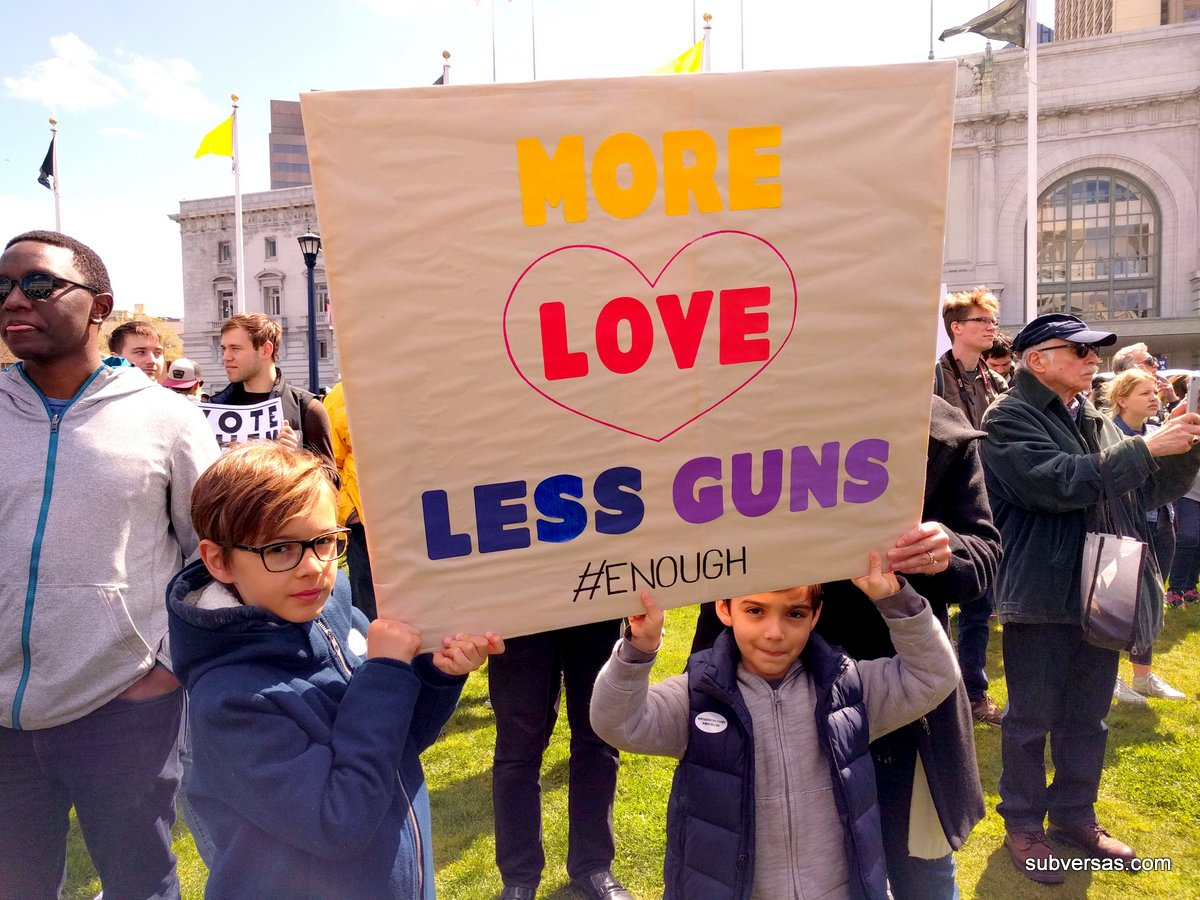 """Two young boys holding sign: """"More love less guns"""""""
