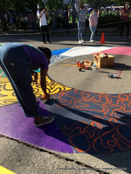 artist painting the giant BLM mural at CHAZ