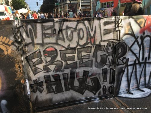 """""""Welcome Free Cap Hill"""" graf in big block letters"""